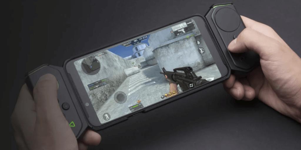 pessoa jogando no celular com um controle para celular.